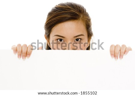 A pretty young asian woman looks over a blank sign