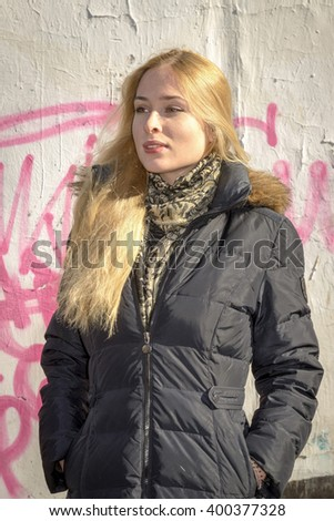 A pretty young blond woman posing outdoors in an urban setting. - stock photo