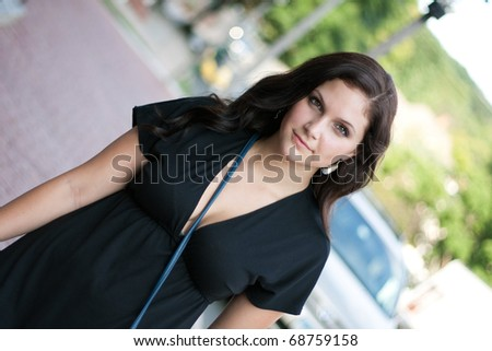 A pretty young brunette woman walking in the city.