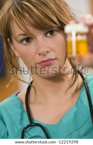 A pretty young female doctor in scrubs with a stethoscope examines a sample pot intently