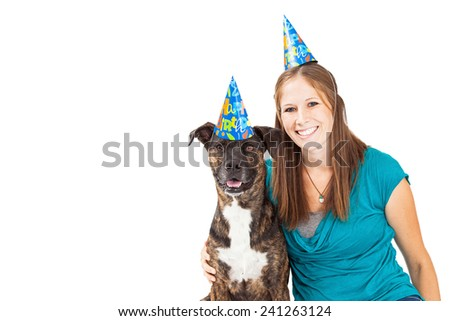 A pretty young girl holding onto a cute mixed breed dog. Both are wearing festive party hats.