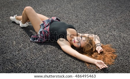 A Pretty young girl laying on asphalt