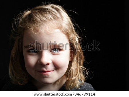 A pretty young girl looking to the side on black - stock photo