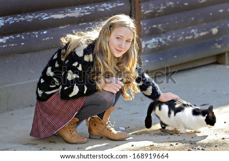 A pretty young girl petting a barn cat while it eats.