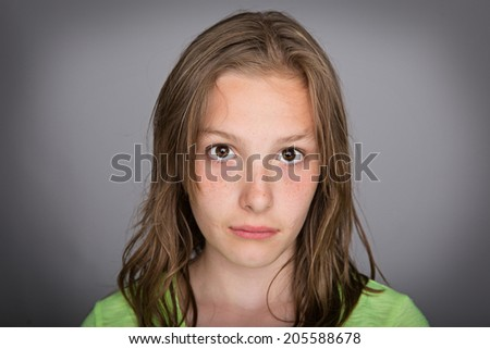 A pretty young girl with a sad expression on her face. - stock photo