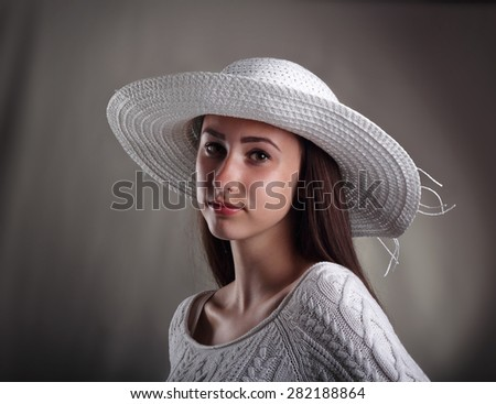 A pretty young model in a white knit sweater and white hat against a grey background.
