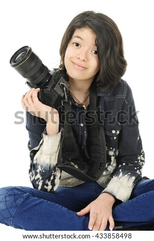 A pretty young teen happily sitting with her pro camera by her shoulder.  On a white background. - stock photo