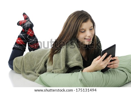 A pretty young teen playing on her iPad while laying on her belly with a pillow and blanket.  On a white background.