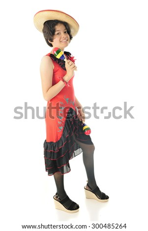 A pretty young teen shaking maracas while happily posing in a red and black Mexican dress and sombrero.  On a white background. - stock photo