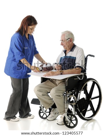 A pretty young volunteer passing a covered meal to a senior man in a wheelchair.  On a white background.