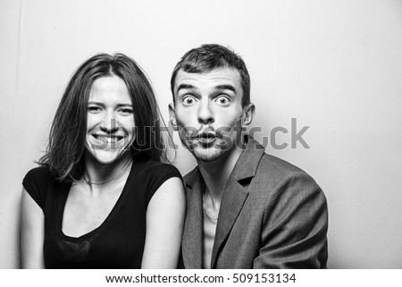 A pretty young white girl and a funny young white guy with different emotion. Love. Laughter and surprise. Black and white photo.