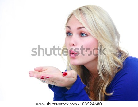A pretty young woman blowing with open palms, isolated on a white background. - stock photo