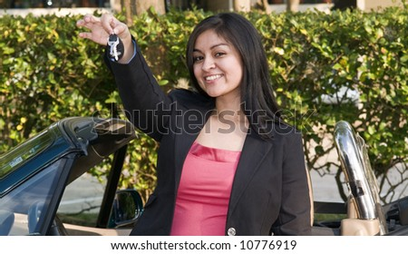 A pretty young woman holding out a set of car keys. - stock photo