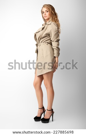 A pretty young woman in an autumn a raincoat. Photo-shoot executed in the studio. - stock photo