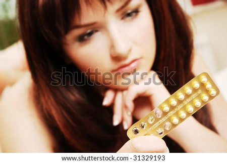 A pretty young woman looking at her contraceptive pills. Shallow depth of field, the focus is on the pills. - stock photo