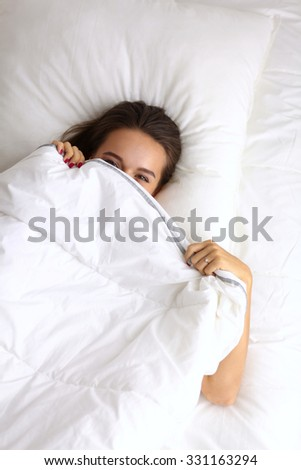 A pretty young woman peeking from under the covers in her bedroom happilly
