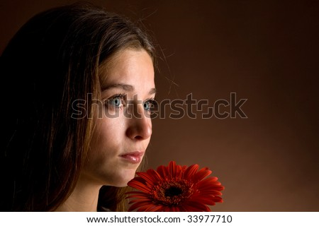 A pretty young woman with long brown hair posing with a red flower in her hand on a dark background
