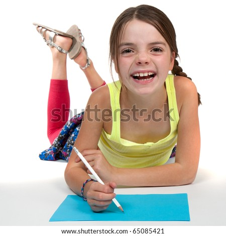 A primary aged girl laughing whilst drawing on some blue paper.