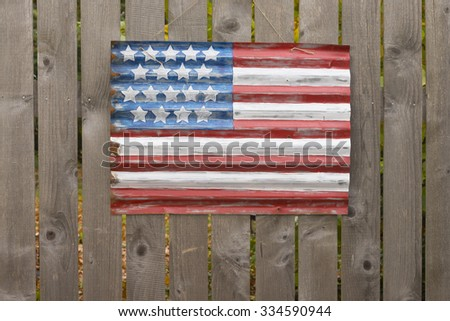 A primitive style American flag painted on a piece of galvanized siding hangs on a wooden fence. - stock photo