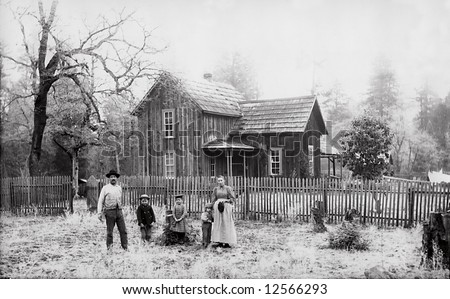 A print from a glass negative taken in an an old view camera about 1890. A family standing in front of their farm house. - stock photo