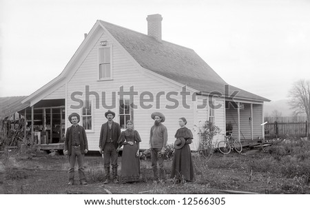 A print from a glass negative taken in an an old view camera about 1890. A family standing in front of their house. - stock photo