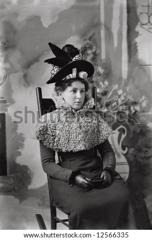 A print from a glass negative taken in an an old view camera about 1890.Lady with great hat seated. - stock photo