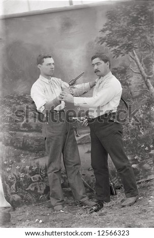 A print from a glass negative taken in an an old view camera about 1890. Two men pointing guns at each other. - stock photo