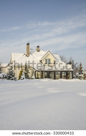 a private house and its garden under snow in winter - stock photo