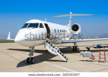 A private jet sits open on the tarmac anticipating the arrival of a couple of pilots.