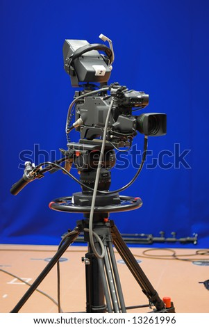 A professional broadcasting television camera in front of a blue screen in a studio.