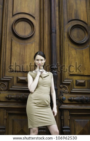 A professional business woman is thinking with a finger pointing to her face, standing in the front of a solemn, ancient styling office door./Let me think - stock photo