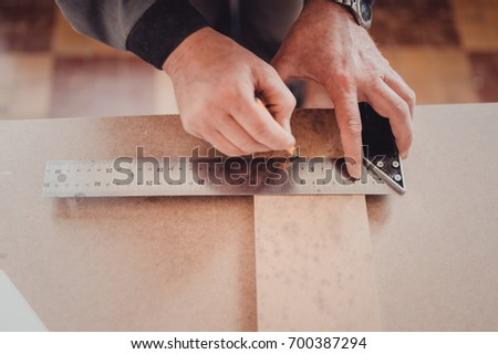 A professional carpenter in the workshop makes measurements of the product with a measuring tape measure. A carpenter uses a framing square for marking a hole in a furniture part. close