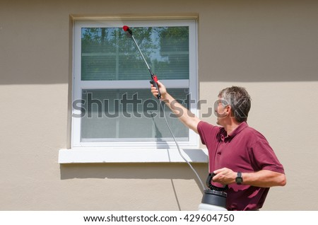 A professional commercial pest control service provider man or do-it-yourself home owner spraying pesticide on the outside of the house to keep bugs and pests out. - stock photo