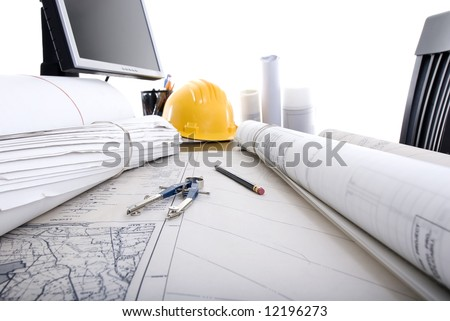 A professional desktop of an Engineer with drawings computer.