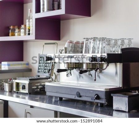 A professional espresso coffee maker, ideal for cafes and bars. Stored over it are late glasses and a waffle maker next to it - stock photo