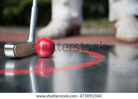 A professional minigolf player starts to hit the ball. Reflections are visible at the ground.