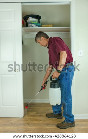 A professional pest control service man or do-it-yourself home owner spraying pesticide on the inside of a house to keep bugs out. - stock photo