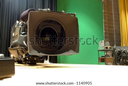 A professional video camera sits waiting in the studio with green screen backdrop.