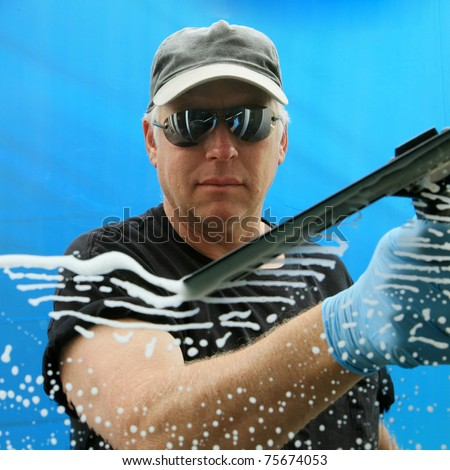 a professional window cleaner soaps and squeegies a window clean - stock photo
