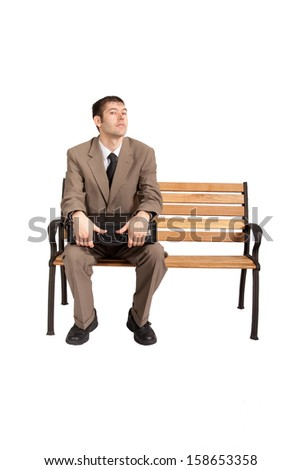 A professionally dressed man holds a briefcase on his lap while looking at the viewer with a slight frown. He may be waiting to complete a business deal or waiting to head off to an interview.  - stock photo