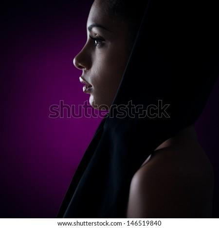 A profile of a beautiful Afro-American woman wearing a headscarf. - stock photo