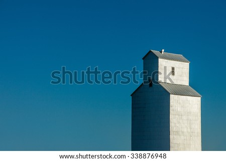 A profile of an old grain elevator against a clear, steel blue sky.