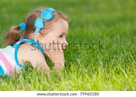A profile portrait of a cheerful little girl on the green lawn