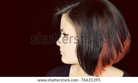A profile portrait of a young woman with funky hair. - stock photo