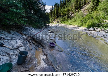 A prospector's tools revealed some gold in a bedrock crack in the high Alaskan mountains - stock photo