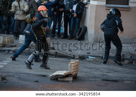 A protester throws a stone towards the pro-government forces during riots in Kiev, Ukraine, February 18, 2014