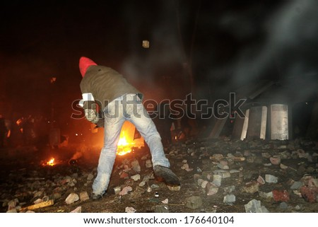 A protester throws stones at police. Kyiv, Ukraine, January 19, 2014 - stock photo
