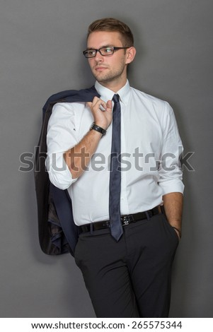 A protrait of a handsome young businessman wearing glasses and smiling. Vertical shot. - stock photo