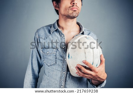 A proud blue collar worker is holding a hard hat - stock photo