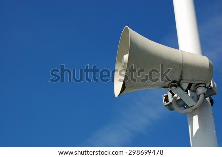 A public address system speaker against a blue sky on a sunny day with space for copy - stock photo